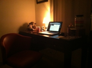my writing space in dramatic lighting. pictured on the laptop is this blog post as I am writing it.